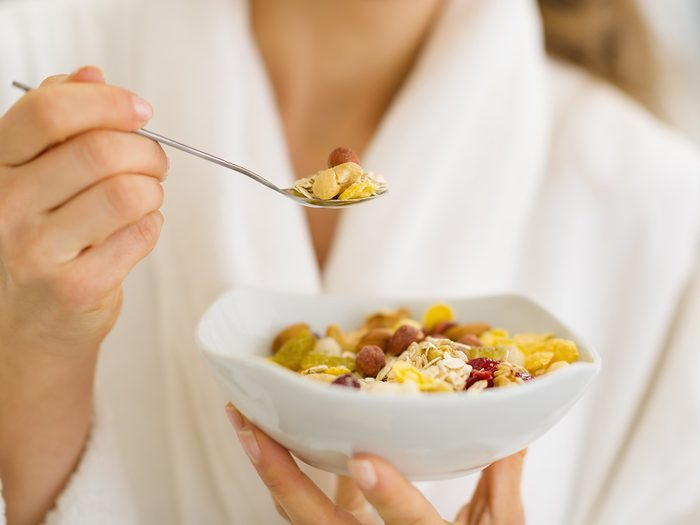 High cholesterol, woman in robe eating bowl of nut cereal