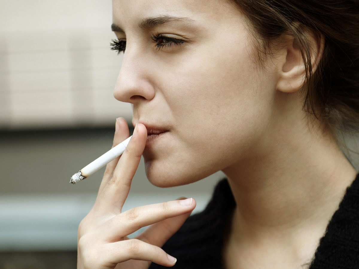 High cholesterol, young woman smoking outside