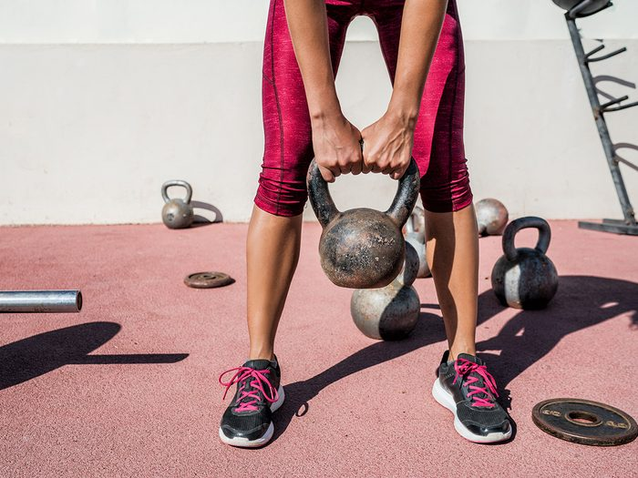 Female athlete with kettlebell working out in outdoor gym