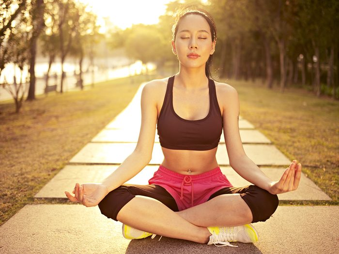 Meditation, a female runner sits and meditates in the middle of the sidewalk