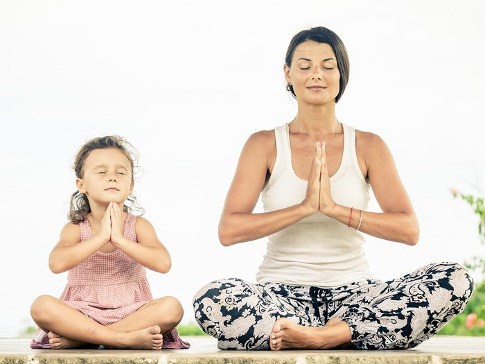 Meditation, woman meditating in a crossed legged position with her daughter