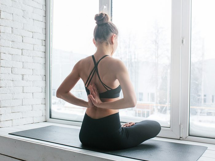 Meditation, woman meditates in front of window