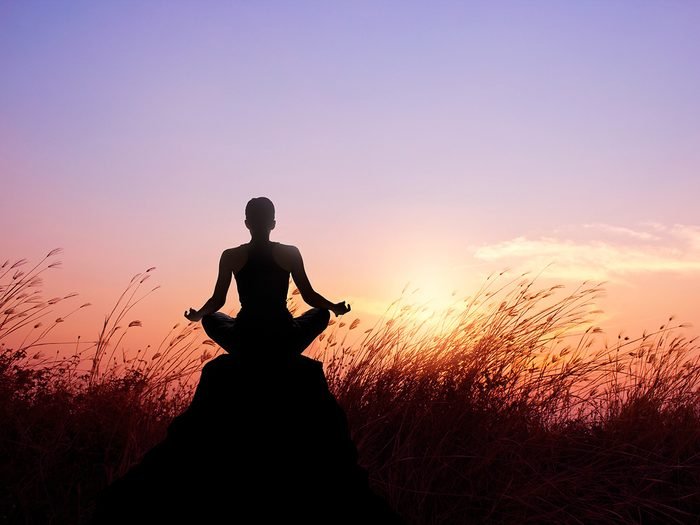 Meditation, Woman meditating at sunrise in a field
