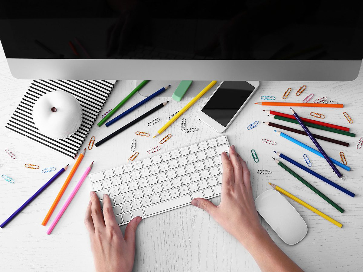 Productivity image. Woman typing at her computer keyboard with a desk covered in coloured pencils.