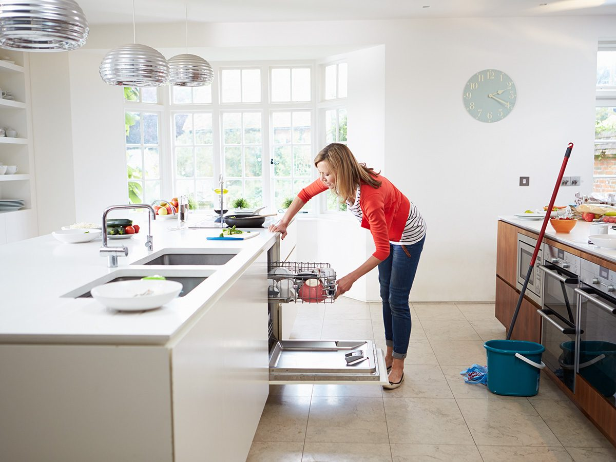 Productivity, a woman unloads her dishwasher in a spacious kitchen