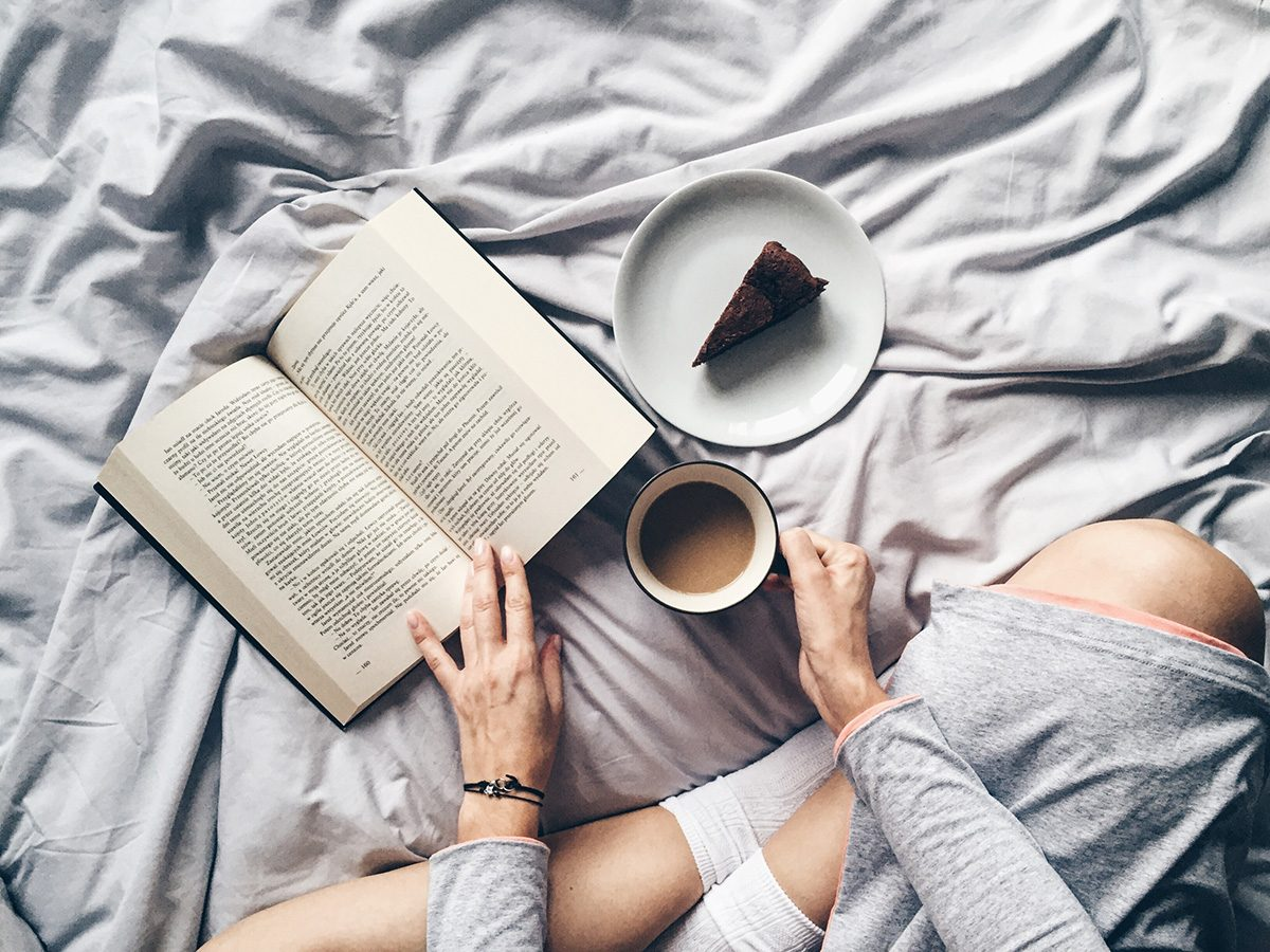 Productivity, Woman sitting in bed drinking coffee, eating cake and reading a book. Shot from above.