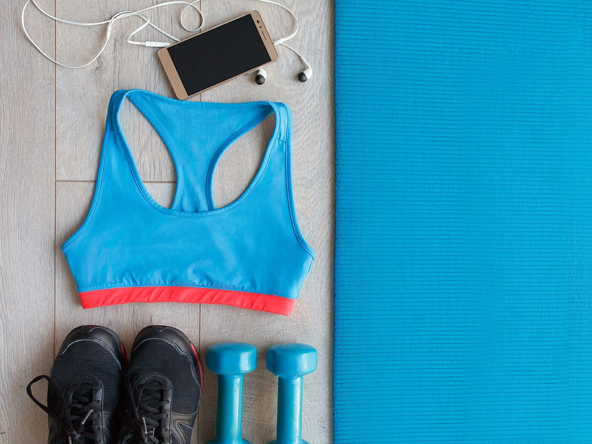 Productivity, a blue yoga mat, blue gym bra, cell phone with earbuds, blue weights and black runners