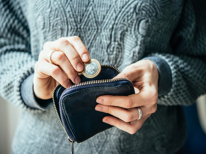 Happiness, woman putting change into a coin purse