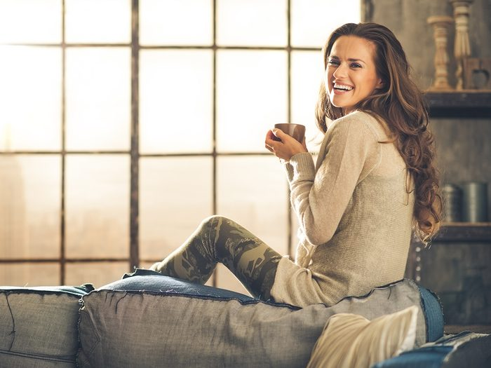 Happiness, woman sitting on couch with cup off coffee and smling