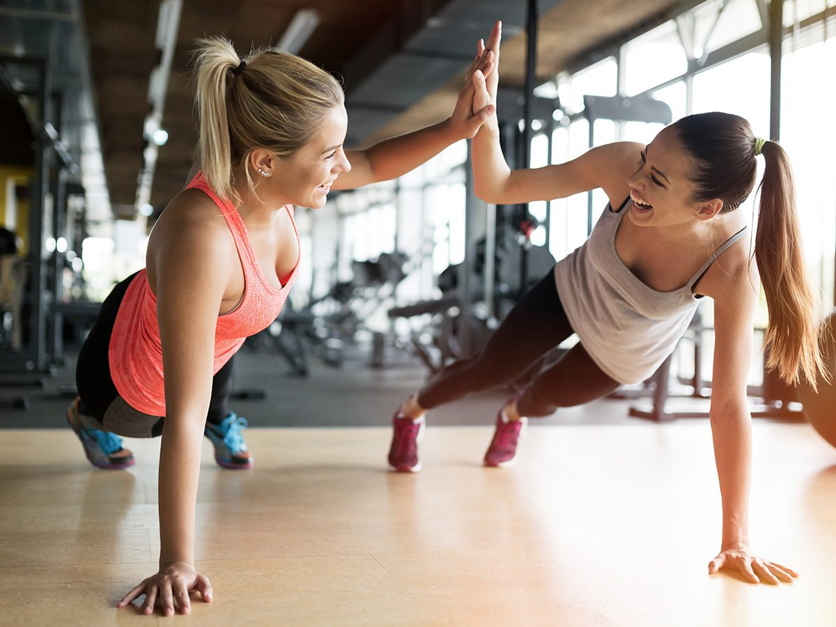 Happiness, two young women high five as they do planks at the gym