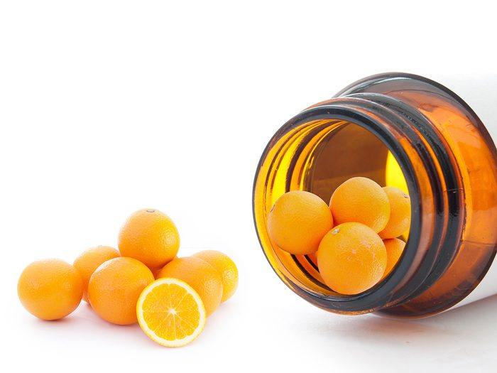 Biotin, vitamin C tablets that look like mini oranges roll out of a pill bottle