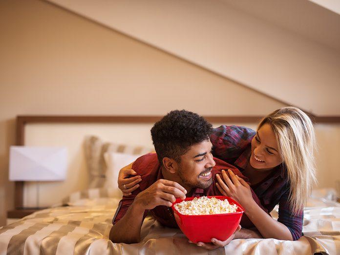 Healthy snacks, couple lying on bed eating popcorn