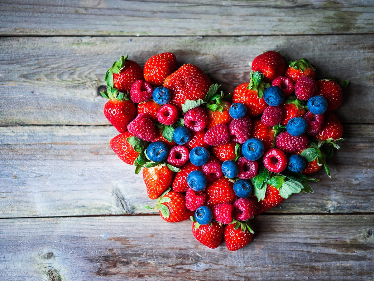 Heart disease, berries gathered into the shape of a heart on a wooden table