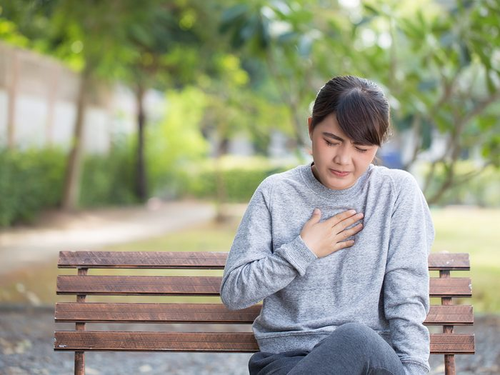 Woman with heartburn clutching her chest on a park bench outside
