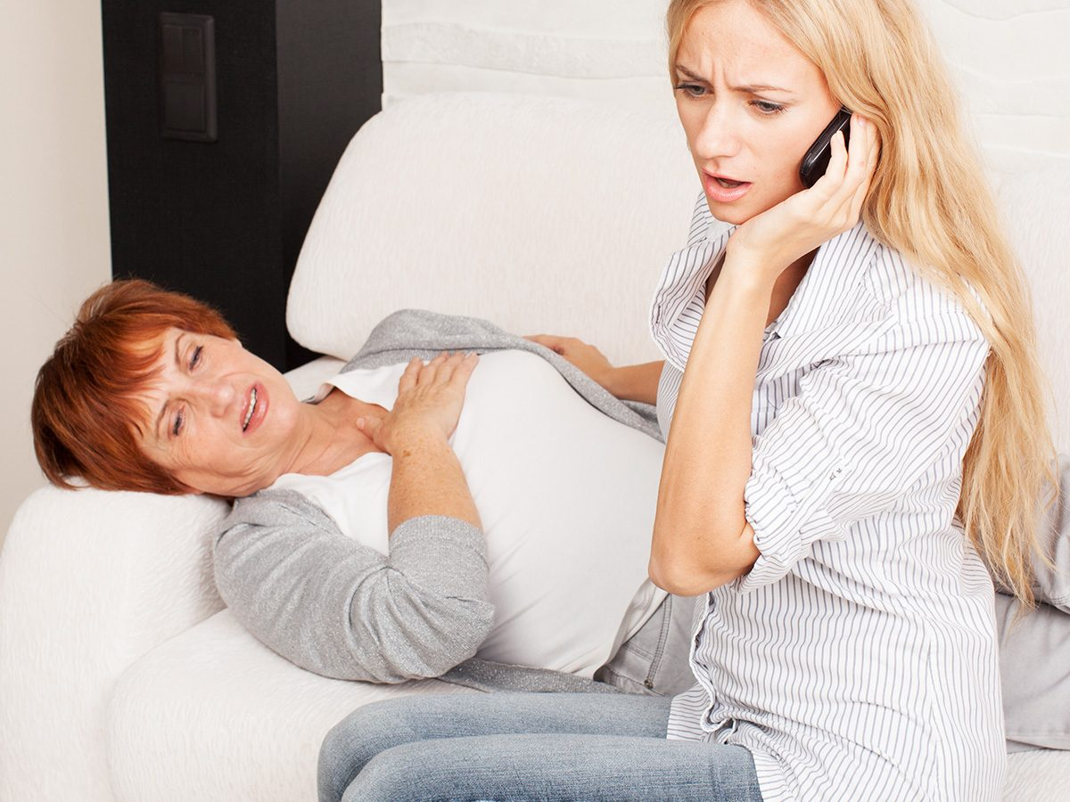 A woman lies on a couch clutching her chest while another woman calls 911, heartburn or heart attack?
