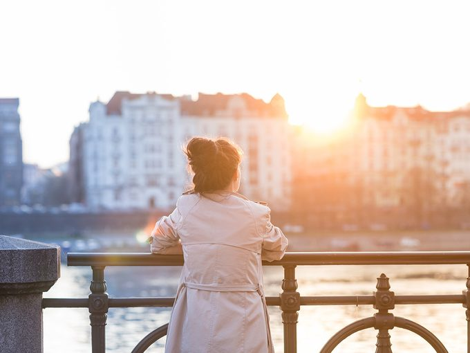 Intelligence, woman standing on bridge looking out over city as sun rises