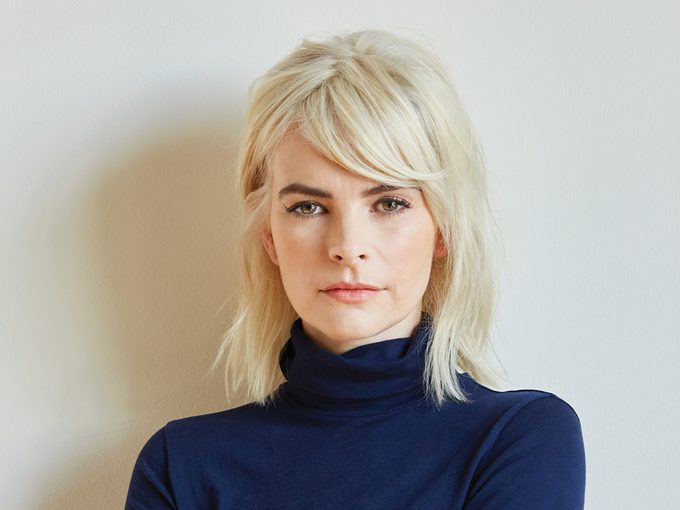 Kelly Oxford with bleach blonde hair wearing a blue turtleneck