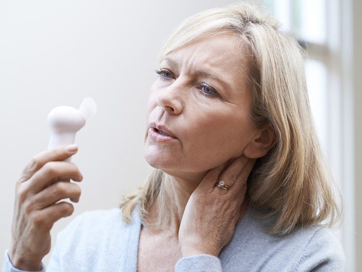 Menopause symptoms, sweating middle-aged woman fans herself with small electric fan