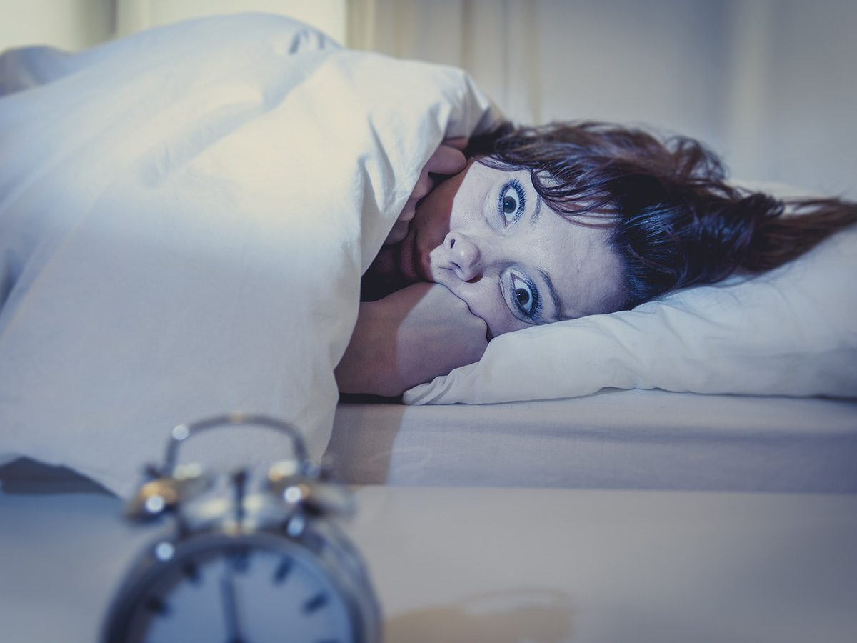 Menopause symptoms, woman lies in bed wide awake and stares at alarm clock because she can't sleep