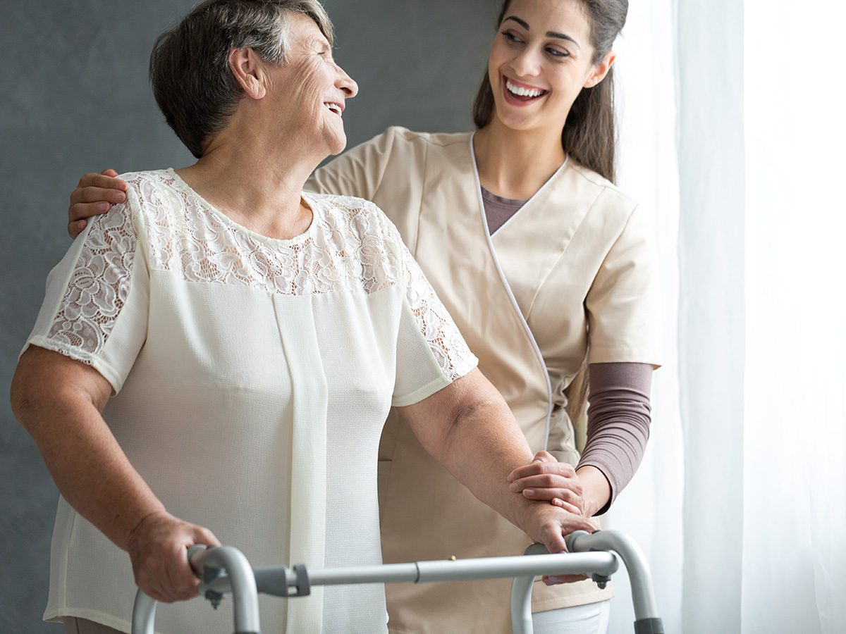 Osteoporosis, elderly woman walks in hospital with a walker
