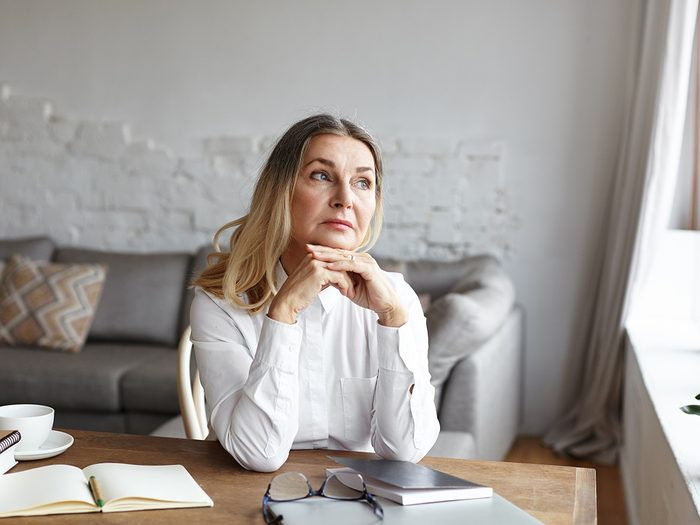 Weight gain, mature woman sits at a table looking sad