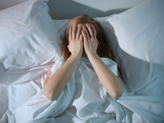Weight gain, woman lies in bed with hands on her face