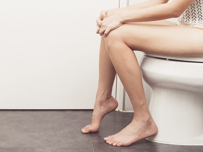 Weight gain, constipated woman sits on toilet