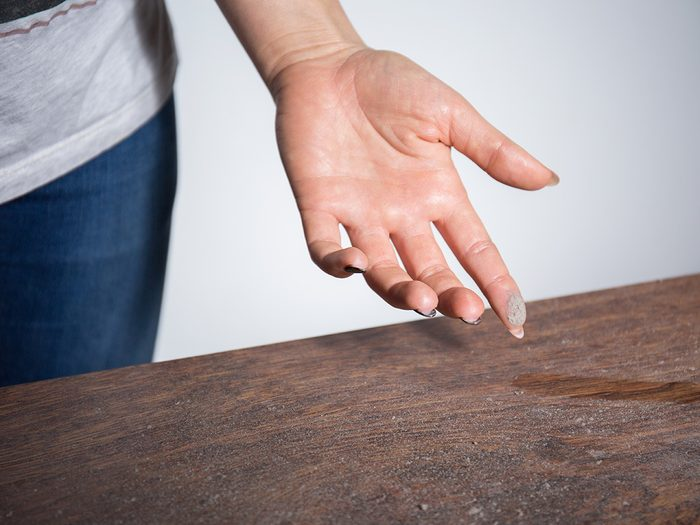Allergies, woman running finger over dusty table