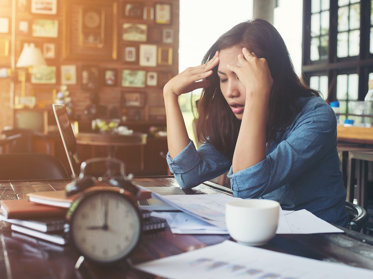Eczema, woman is very stressed at her desk