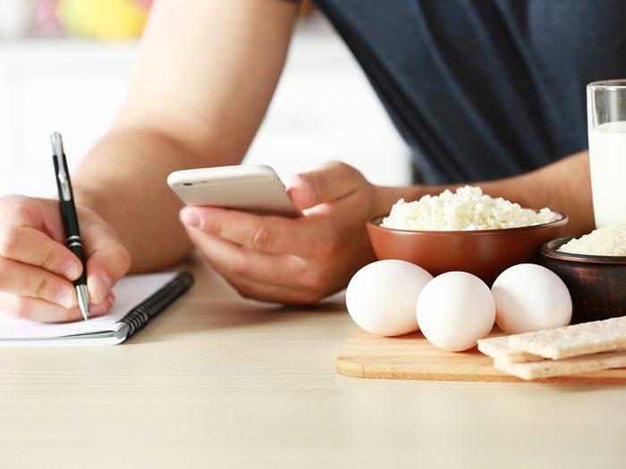 Healthy food, man counting calories at a table