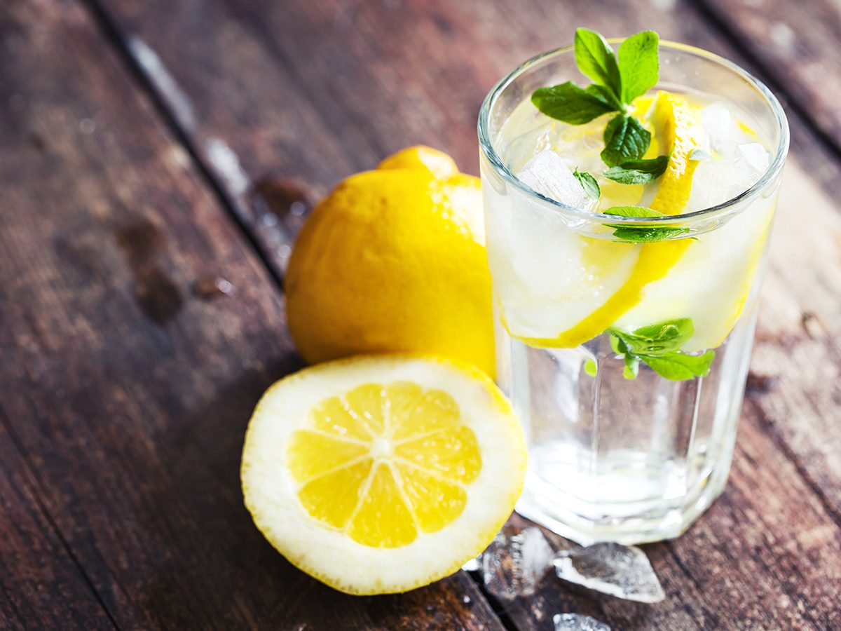 Healthy foods, a glass of lemon water with cut up lemons next to it