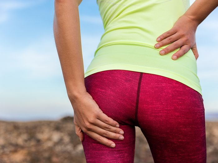 Muscle pain relief, woman holds her sore butt