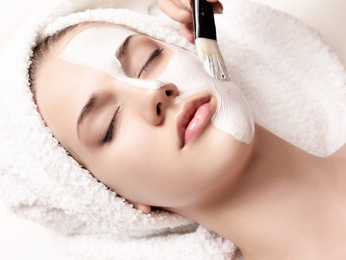 A woman has a professional skin peel applied to her face