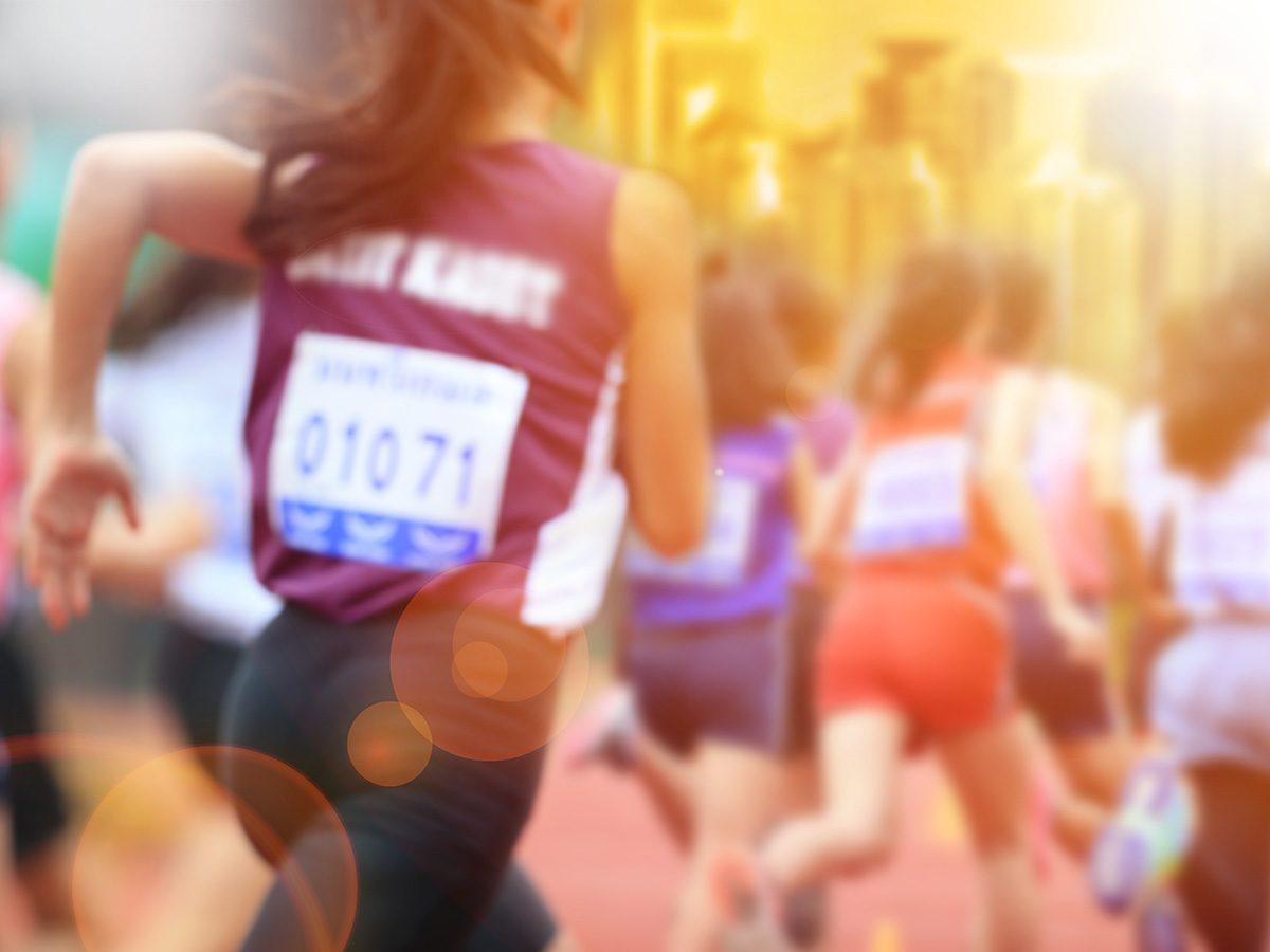 Self love, blurry back of a woman as she runs a marathon