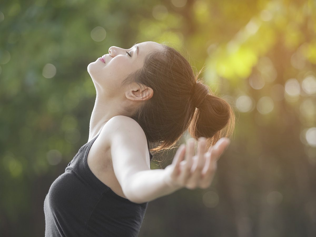 Shortness of breath, Woman breathes deeply and throws her arms wide outdoors