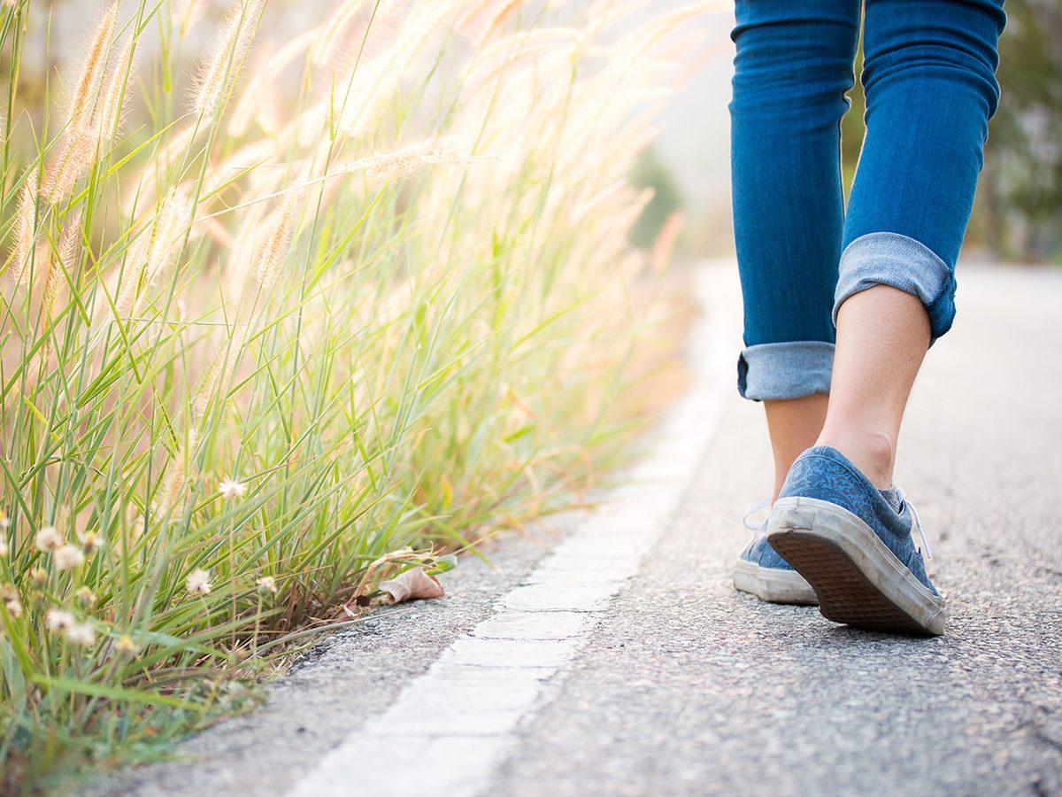 Shortness of breath, woman walking alongside a field of long grasses
