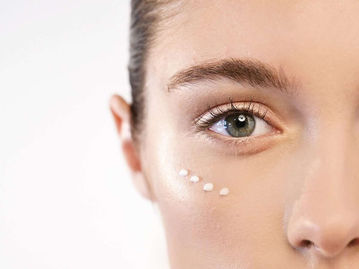 Skin, woman with eye cream dotted under her eyes