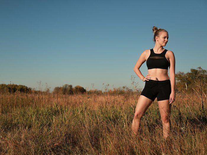 Workout gear, Woman standing in a field wearing black Lunapads sport shorts