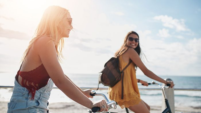 Happy People, two girls riding bikes
