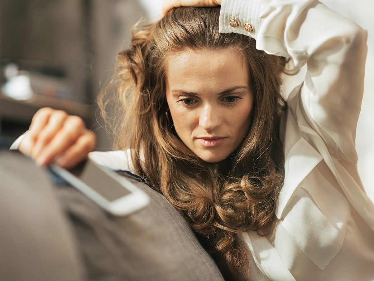 Woman with anxiety is very stressed, holding her cell phone