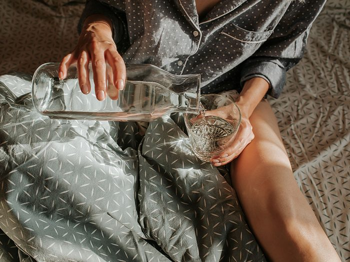 detox naturally | woman drinking water in bed