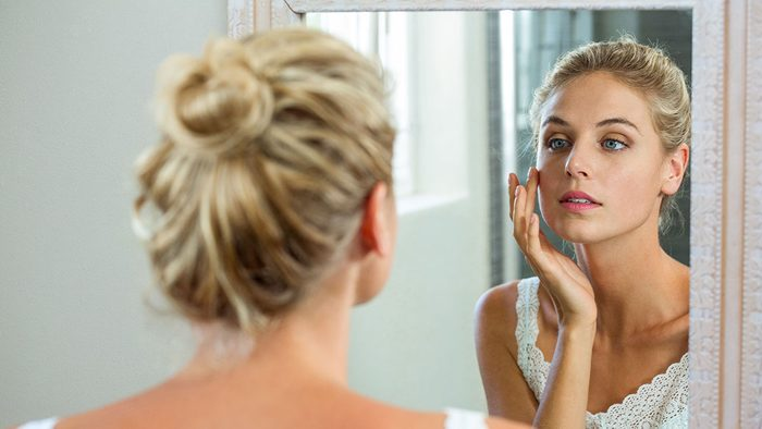 Itchy Scalp, woman looking in the mirror