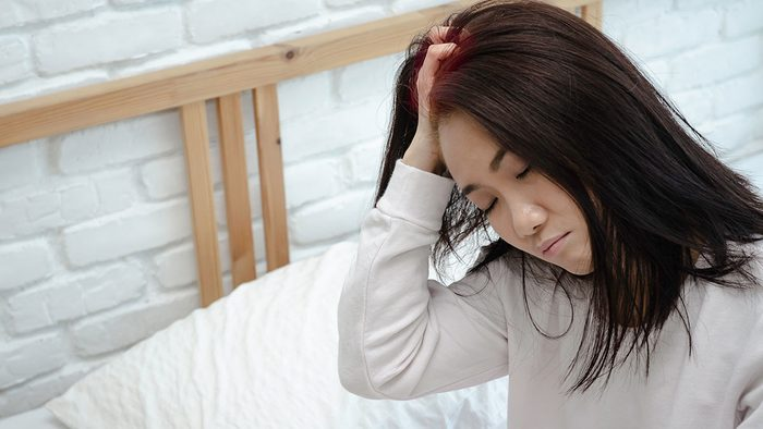 Itchy scalp, woman stressed