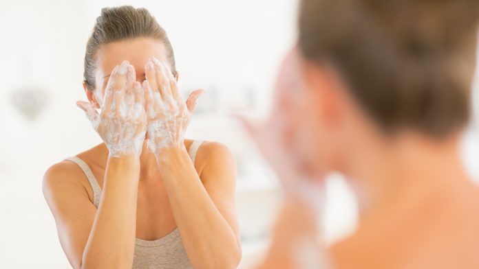 woman exfoliates her face to protect against skin damage from pollution