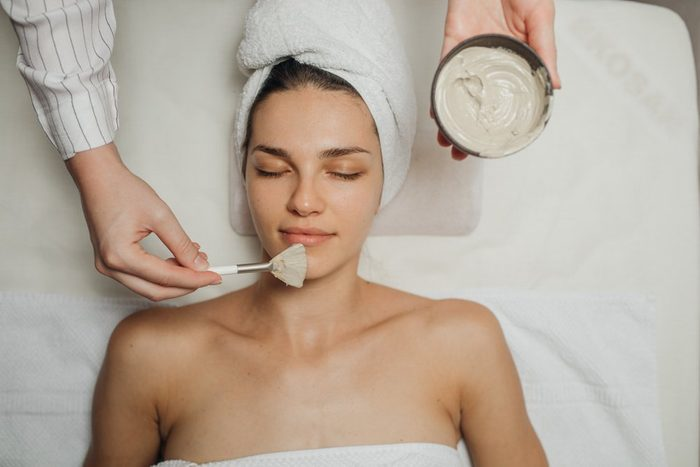 Hands of a Caucasian cosmetologist woman applying a facial mask on a beautiful young Caucasian woman's face lying on the massaging bed.