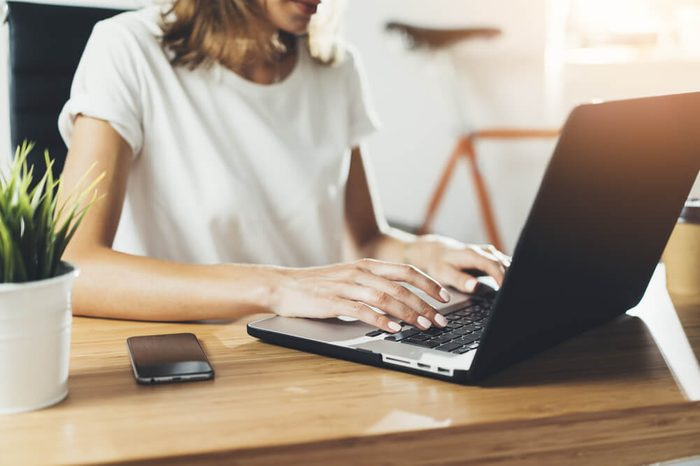 Close-up image of young professional female manager using laptop at her office, businesswoman working from home via portable computer, hipster girl freelancer writing on keyboard, flare light