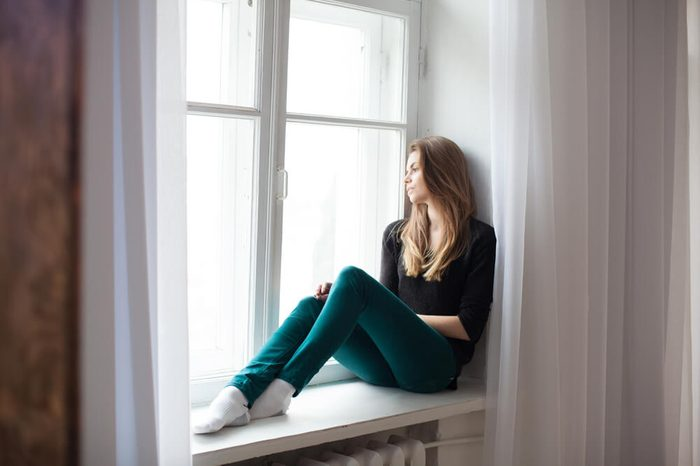 the girl sitting by the window watching the street