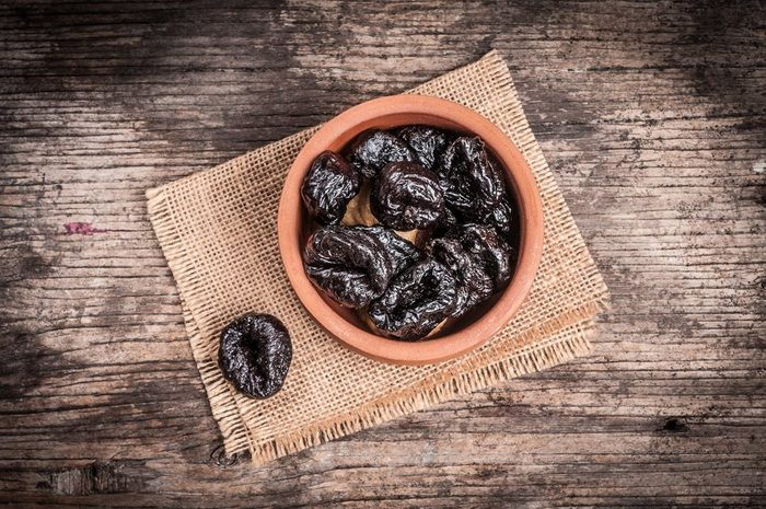 Prunes in bowl on linen and rustic wood