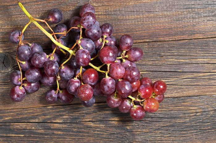 Red grapes on old wooden table, top view