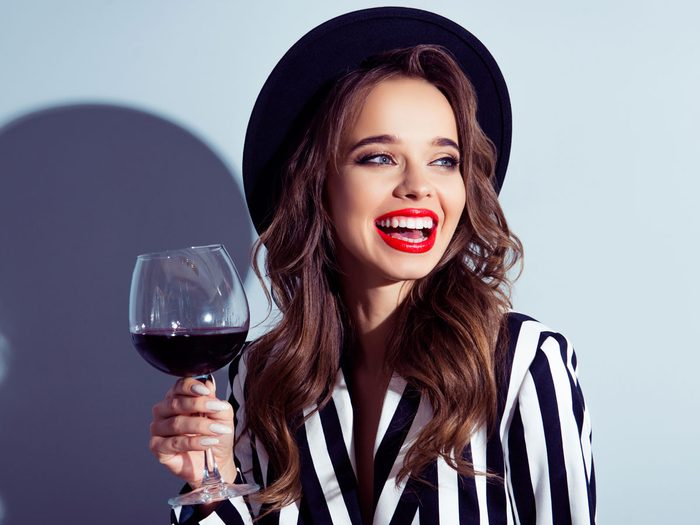 woman drinking wine with a smile and white teeth